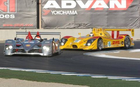An Audi R10 and Porsche RS Spyder come out of Turn 11 to begin a run down the front straight.