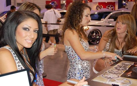 Hair, Fashion accessory, Dress, Office equipment, Necklace, Brown hair, Luxury vehicle, Layered hair, Auto show, Desk,