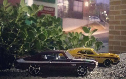 Two muscle cars stalk a parking lot.