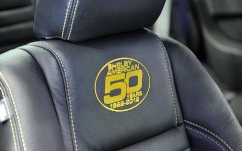 Motor vehicle, Car seat, Logo, Leather, Head restraint, Car seat cover, Symbol,