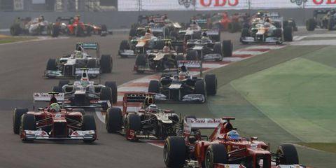 2012 Indian Grand Prix: Fernando Alonso, Ferrari F2012, leads Felipe Massa, Ferrari F2012, Kimi Raikkonen, Lotus E20 Renault, Sergio Perez, Sauber C31 Ferrari, Pastor Maldonado, Williams FW34 Renault, and the remainder of the field through the first corner.