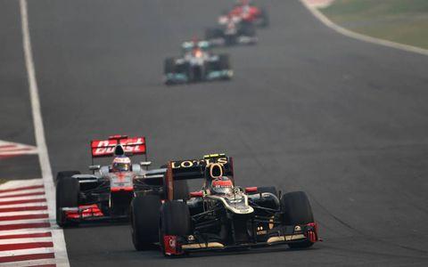 2012 Indian Grand Prix: Romain Grosjean, Lotus E20 Renault, leads Jenson Button, McLaren MP4-27 Mercedes.