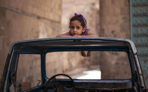 Looking forward  // Yemen continues to face economic hardship and political uncertainty following the February departure of president A. Abdullah Saleh. Here, a young girl rests on the roof of an abandoned car in Sana'a, Yemen's old city.