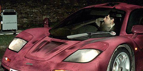 Actor Rowan Atkinson is shown driving his McLaren F1 sports car.