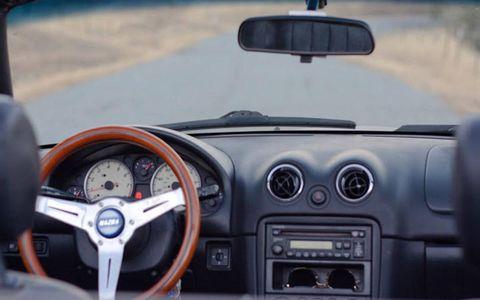 The simple, uncluttered dash of a 2000 Mazda Miata.