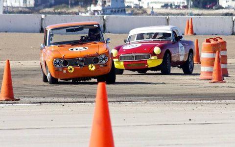 Bill Noon leans his '63 Alfa Romeo Guilia TI into Corner 8 to keep ahead of Jeffrey Herr's '66 MGB.