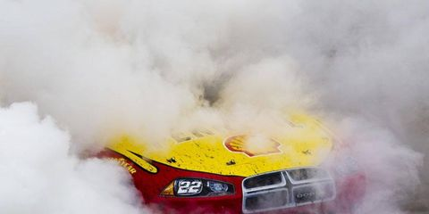 Clouds of tire smoke envelop Kurt Busch's race car after he won the NASCAR race at Dover on Sunday.