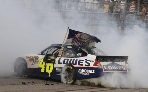 Jimmie Johnson celebrates his fifth NASCAR trophy with a burnout on the Homestead-Miami track.