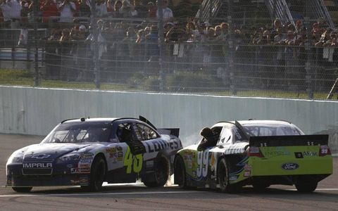 Season champion Jimmie Johnson meets race winner Carl Edwards on the Homestead-Miami track after the race.