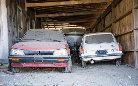 A Peugeot 505 Turbo and an MGB GT sit in a shed.