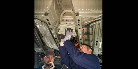 General Motors workers install a structural reinforcement in the battery-tunnel area of a Chevrolet Volt.