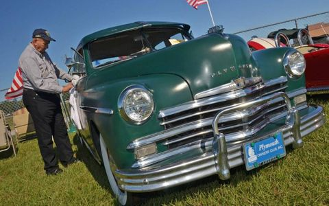 John Jankowich polishes his 1949 Plymouth Special Deluxe sedan. The car is a survivor, it has only received mechanical restoration, and manages to still have a full, if dull, patina of green paint.