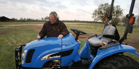 Former President George W. Bush adds his signature to Lil Tug, the tractor from Jay Leno's garage that will be sold at the Barrett-Jackson auction.