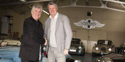 Charles Morgan (right) and Jacques Nicolet shake hands in Morgan's garage. Morgan sports cars will race in the Le Mans 24 Hours this season.