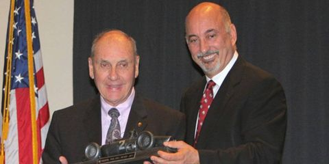 George Follmer, left, received the Phil Hill Award from Road Racing president Bobby Rahal at the club's annual dinner at Daytona, Fla.