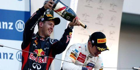 Race-winner Sebastian Vettel, left, celebrates on the podium with Kamui Kobayashi in Japan on Sunday.