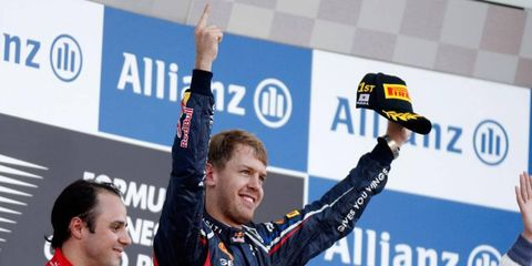 Sebastian Vettel celebrates on the top rung of the podium at Suzuka.