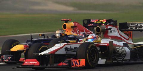 Sebastian Vettel puts a lap on Narain Karthikeyan during the India Grand Prix.