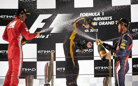 Fernado Alonso, left, Kimi Raikkonen, center, and Sebastian Vettel celebrate on the podium Sunday in Abu Dhabi.