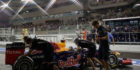 Crew members attend to Sebastian Vettel's car following qualifying in Abu Dhabi on Saturday.