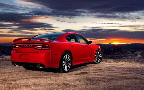 The long, clean lines of the 2012 Dodge Charger SRT8 contribute to its muscular look. Bright reddish-orange paint hints at its performance potential.