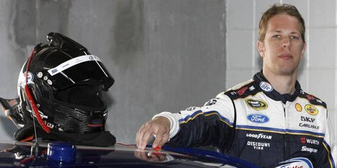 Brad Keselowski poses with his new car and his new fire suit.