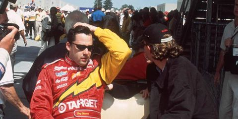 """In a photo from 2001, Tony Stewart is rushed away in a golf cart after finishing the Indy 500. He then flew to Charlotte to compete in the NASCAR race. He's got an offer to do the """"double"""" again this year."""