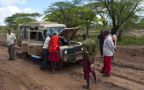Slogging through deep mud, our Land Rover Defender overheated. Some Masai people came to our aid with a couple of gallons of water.