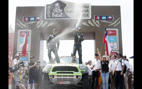 VICTORY SHOWER // French drivers Stéphane Peterhansel (right) and his co-driver Jean Paul Coltret shower the crowd with champagne to celebrate their Rally Dakar win in Santiago, Chile.