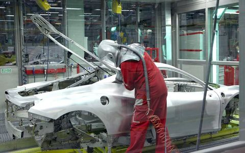 A worker fine tunes the fit of the rear hatch on a 458 Italia.
