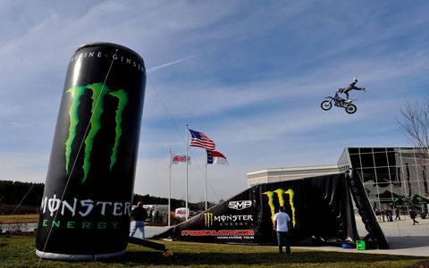 Superman // A Monster Energy drink Moto X rider performs a trick during the Monster sponsorship announcement at Kyle Busch Motorsports on Jan. 19 in Mooresville, N.C. Photo by: Nigel Kinrade/LAT Photographic