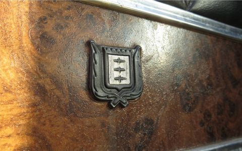 """Nothing says """"luxury"""" like a plastic crypto-heraldic emblem on plastic wood."""