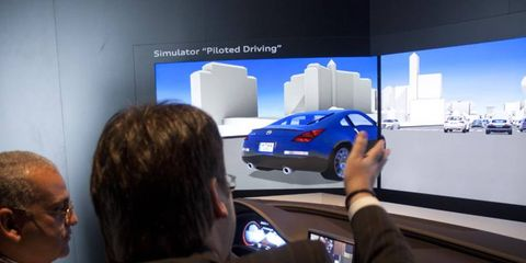 In a simulator, an Audi rep shows a journalist how Piloted Driving can avoid beaning Nissans.