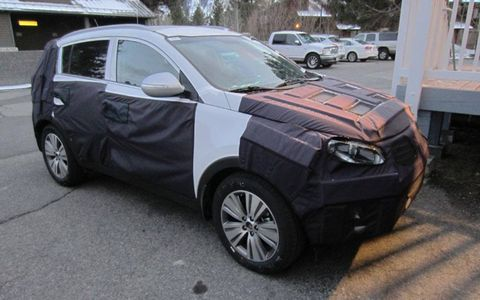 Despite the camouflage, the roofline and pillars give this away as a Kia Sportage crossover.