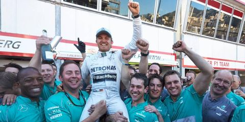 Nico Rosberg, celebrating with Mercedes mechanics, scored a win at Monaco 30 years after his father Keke pulled off that feat.