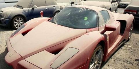 An abandoned Ferrari Enzo was seized in Dubai after several months in a car park collecting dust. Photo by Nigel Smuckatelli.