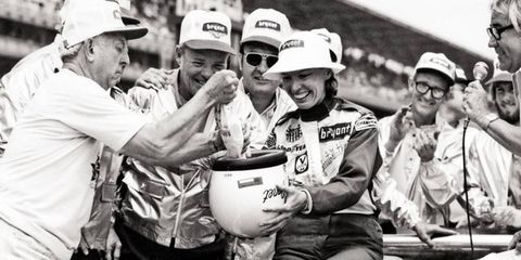 Phil Hedback, a Bryant heating and cooling dealer and car sponsor, pours 188 silver dollars into Janet Guthrie's helmet in honor of her race-making qualifying speed at the 1977 Indy 500.