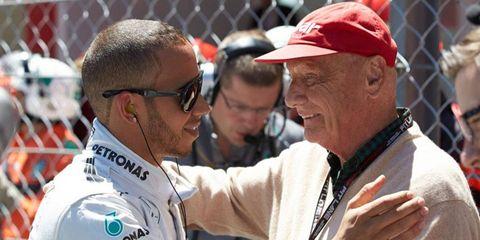 Three-time Formula One champion Nikki Lauda, right, visits with Lewis Hamilton earlier this season.