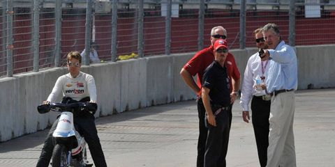 Izod IndyCar Series driver Will Power, left, surveys the track in Houston as officials huddle to determine their next course of action.