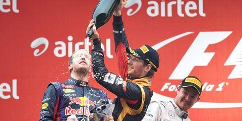 Romain Grosjean pours champagne on Formula One champion Sebastian Vettel as Nico Rosberg looks on Sunday.