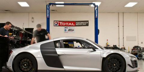 Crew members work on Paul Miller Racing's Audi R8 LMS that it will race in the 2014 Tudor United SportsCar Championship.