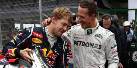 Michael Schumacher, putting his arm around current Formula One champ Sebastian Vettel, is still in an induced coma after suffering a brain injury while skiing.