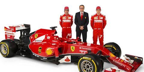 Ferrari boss Stefano Domenicali stands with drivers Fernando Alonso and Kimi Raikkonen in front of the new Ferrari F1 car, the F14-T.