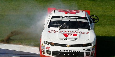 Kyle Larson celebrates in the grass in front of the main grandstand at Auto Club Speedway in Fontana, Calif., on Saturday.