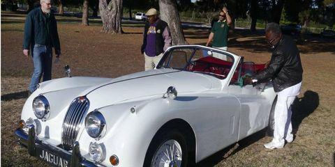 Winston Dabbs puts the finishing touch on his XK140 at The Queen's English car show Sunday.