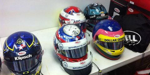 In Bell's gasoline alley garage, helmets (counterclockwise from bottom left) for Josef Newgarden (backup in blue, primary with stars in blue stripe), Jacques Villeneuve, James Davison and Martin Plowman.