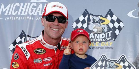 Kevin Harvick and son Keelan celebrate Harvick's track qualifying record at Michigan International Speedway on Friday.