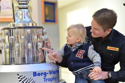 Hunter-Reay holds up son Ryden to look at the Borg-Warner.