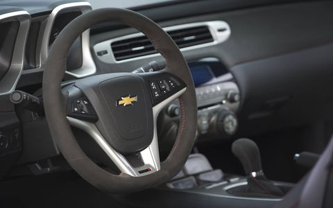 Additional interior features include a thick, flat-bottom steering wheel, alloy pedals and a head-up display with unique performance readouts.