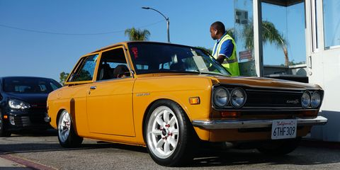 Datsun 510 loaded and lowered pays its 15 bucks to park across the street from the show.